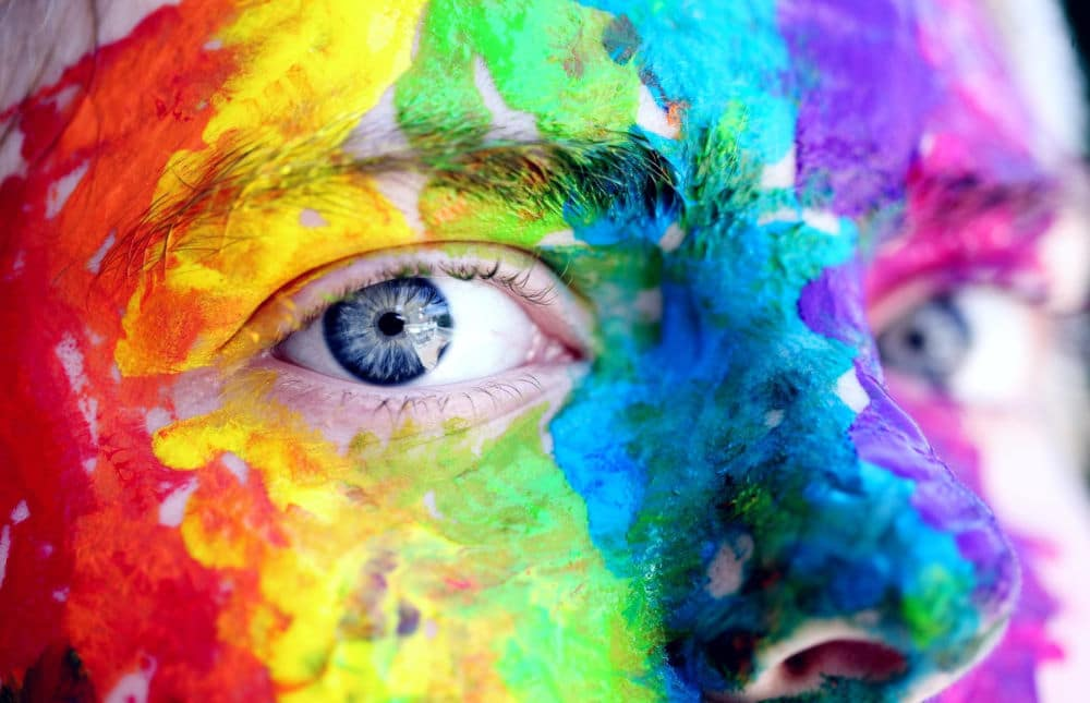Picture of face with many different colors of paint on it